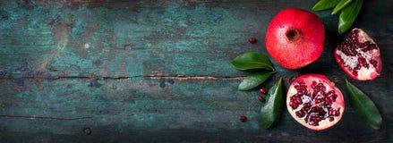 Frischer saftiger Granatapfel - ganz und Schnitt, mit Blättern auf einem hölzernen Weinlesehintergrund, Draufsicht, horizontal Lizenzfreies Stockbild