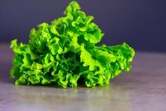 Frischer saftiger Kopfsalat auf einer grauen K?chentischplattennahaufnahme Das Konzept des gesunden Essens lizenzfreie stockfotos