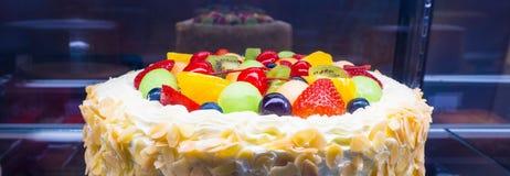 Frischer Sahnekuchen der bunten Mischfrucht im Kühlschrankschaukasten Stockfoto