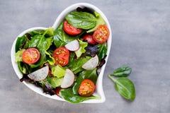 Frischer Salat mit Babyspinat und Tomaten, Rettich und Salat Lizenzfreies Stockfoto