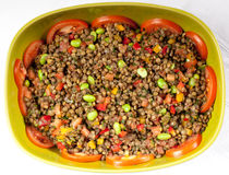 Frischer Salat mit Bohnen und Tomaten in einer grünen Schüssel Stockfotografie