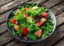 Frischer Salat mit der Hühnerbrust, Arugula, Nüssen und Tomaten auf Schwarzblech in einem Holztisch Lizenzfreies Stockfoto