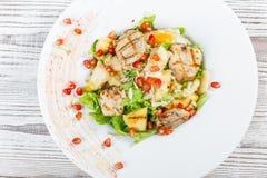 Frischer Salat mit der Hühnerbrust, Melone, Ananas, Granatapfelsamen, Kopfsalatblättern und Mandel auf Platte auf hölzernem Hinte Lizenzfreies Stockfoto