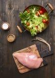 Frischer Salat mit Kirschtomaten, Gewürze und Kräuter, in einem kupfernen Topf, mit der rohen Hühnerbrust auf Schneidebrett, träg Stockfotografie