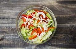 Frischer Salat mit Kräutern, Paprika und Zwiebel in der Glasplatte Lizenzfreies Stockfoto