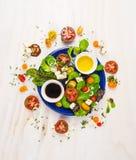 Frischer Salat mit Tomaten, Feta, Balsamico-Essig und Öl in der blauen Platte auf weißem hölzernem Hintergrund Stockbild