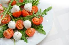 Frischer Salat von Arugula, von Kirschtomaten und von Mozzarella Lizenzfreie Stockfotografie
