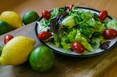 Frischer Salat von den verschiedenen Arten von Gr?ns und von Kirschtomaten, gew?rzt mit Oliven?l und Limettensaft mit Zitrone lizenzfreies stockbild