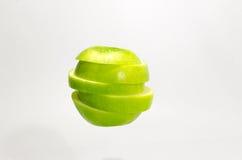 Frischer Scheibengrünapfel auf weißem Hintergrund Lizenzfreie Stockfotografie