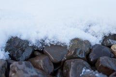 Frischer Schnee, der in den Grobkiesfelsen schmilzt Stockfotos