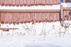 Frischer Schnee schmilzt auf dem Sonne hölzernen Heizzaun stockfotos