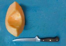 Frischer Schnitt Kantalupenkeil auf blauem Hintergrund mit Messer stockfotografie