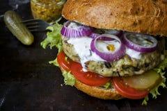 Frischer selbst gemachter Burger mit würziger Soße, cornichons und Kräutern über dunklem Metallhintergrund Stockfotos