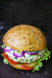 Frischer selbst gemachter Burger mit würziger Soße, cornichons und Kräutern über dunklem Metallhintergrund Stockfoto
