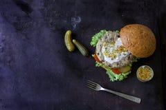 Frischer selbst gemachter Burger mit würziger Soße, cornichons und Kräutern über dunklem Metallhintergrund Lizenzfreie Stockfotos