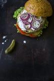 Frischer selbst gemachter Burger mit würziger Soße, cornichons und Kräutern über dunklem Metallhintergrund Lizenzfreie Stockfotografie