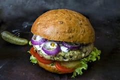 Frischer selbst gemachter Burger mit würziger Soße, cornichons und Kräutern über dunklem Metallhintergrund Stockbild