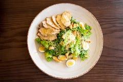 Frischer Sommersalat Caesar mit Ei-, Kopfsalat-, Hühner- und Parmesankäseparmesankäse auf weißer Platte auf hölzernem Hintergrund Stockfotos
