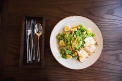 Frischer Sommersalat Caesar mit Ei-, Kopfsalat-, Hühner- und Parmesankäseparmesankäse auf weißer Platte auf hölzernem Hintergrund Lizenzfreies Stockfoto