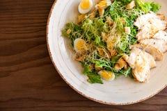 Frischer Sommersalat Caesar mit Ei-, Kopfsalat-, Hühner- und Parmesankäseparmesankäse auf weißer Platte auf hölzernem Hintergrund Lizenzfreie Stockbilder