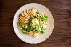 Frischer Sommersalat Caesar mit Ei-, Kopfsalat-, Hühner- und Parmesankäseparmesankäse auf weißer Platte auf hölzernem Hintergrund Lizenzfreie Stockfotografie