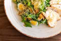 Frischer Sommersalat Caesar mit Ei-, Kopfsalat-, Hühner- und Parmesankäseparmesankäse auf weißer Platte auf hölzernem Hintergrund Lizenzfreies Stockbild