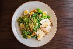 Frischer Sommersalat Caesar mit Ei-, Kopfsalat-, Hühner- und Parmesankäseparmesankäse auf weißer Platte auf hölzernem Hintergrund Stockfoto