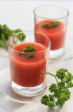 Frischer Tomatensaft in einem Glas auf einer weißen Tabelle Lizenzfreie Stockfotos