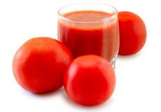Frischer Tomatesaft im Glas und in den Tomaten. lizenzfreies stockfoto