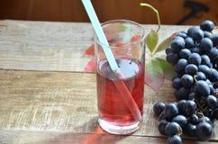 Frischer Traubensaft durch einige Weinreben Bürste von frischem organischem des Traubensafts der blauen Traube auf Holzoberfläche Lizenzfreies Stockfoto