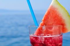 Frischer tropischer Fruchtcocktail mit Wassermelonenscheibe auf einem Strand Lizenzfreie Stockbilder