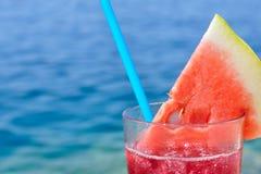 Frischer tropischer Fruchtcocktail mit Wassermelonenscheibe auf einem Strand Lizenzfreie Stockfotos