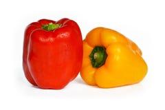 Frischer und reifer roter Paprika vor gelbem Paprika im Hintergrund lokalisiert auf weißem Hintergrund stockbilder