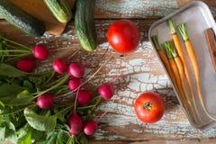 Frisches Bauernhofgemüse - Rettich, Karotte, Gurke und Tomate auf Draufsicht des alten hölzernen rustikalen Hintergrundes Stockbilder