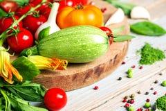 Frisches Bauernhofgemüse und -kräuter auf rustikalem Hintergrund Lizenzfreies Stockfoto