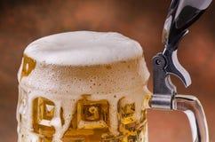 Frisches blondes Bier mit überfließendem Deckel Lizenzfreies Stockbild
