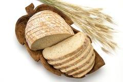 Frisches Brot auf einem geschnitzten Stand mit den Ohren des Weizens auf einem weißen Hintergrund Lizenzfreies Stockfoto