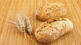 Frisches Brot der ganzen Mahlzeit mit Samen auf hölzernem Hintergrund und Weizen Stockfotos