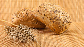 Frisches Brot der ganzen Mahlzeit mit Samen auf hölzernem Hintergrund und Weizen Stockbilder