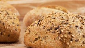 Frisches Brot der ganzen Mahlzeit mit Samen auf hölzernem Hintergrund und Weizen Stockfotografie