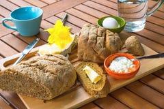 Frisches Brot, Käse, Butter, Ei, Wasser, Tee oder Kaffee auf Küchenbrotschneidebrett auf Holztisch Stockfotografie