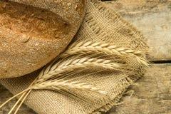 Frisches Brot mit den Weizenähren auf Holztisch Stockbild