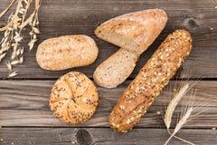 Frisches Brot und Bäckerei auf einer alten Weinlese planked w Lizenzfreies Stockfoto