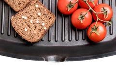 Frisches Brot und Kirschtomaten auf einer Grillwanne stockfotos