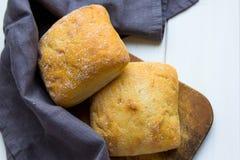 Frisches ciabatta Brot in einem grauen Stoff am hölzernen Schreibtisch stockbilder