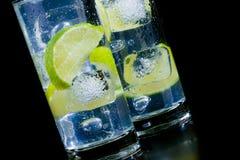 Frisches Cocktail mit Eis- und Kalkscheibe auf schwarzer Tabelle Stockfotografie
