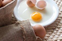 Frisches defektes Ei mit Eigelb auf weißem Teller, rohe Eier mit Eisackleinen in der braunen Tasche, fotografiert auf hölzernem H lizenzfreie stockfotos