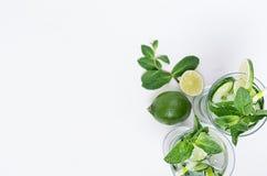 Frisches Detoxfrühlingscocktail mit Minze, Kalk, Eis, Gurke, Stroh als Grenze auf weichem weißem hölzernem Brett, Draufsicht stockbilder