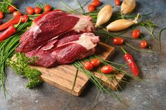 Frisches dunkles Fleisch mit Bestandteilen für das Kochen auf braunem hölzernem Schneidebrett lizenzfreie stockfotos