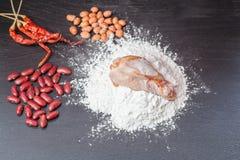 Frisches Ei im Mehl, in den Erdnüssen mit rote Linsen Huhn und im hölzernen Rollen auf schwarzer Tafel Lizenzfreie Stockfotografie